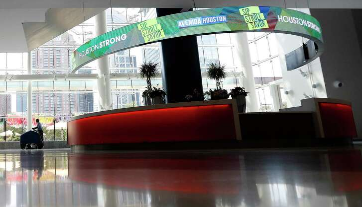 A man cleans the floor in the hallway of the George R. Brown Convention Center, which was nearly empty on Friday.