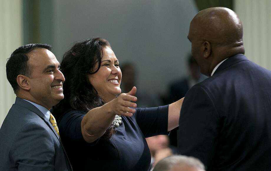 """Assemblywoman Lorena Gonzalez Fletcher, D-San Diego, flanked by Assemblyman Ash Kalra, D-San Jose, left, goes to hug Assemblyman Jim Cooper, D-Elk Grove, for his vote for the """"sanctuary state"""" bill she carried in the Assembly Friday, Sept. 15, 2017, in Sacramento, Calif. The Assembly approved the bill, SB54, by Senate President Pro Tem Kevin de Leon, D-Los Angeles, that would limit police cooperation with federal immigration authorities. It now goes to the Senate for final approval.(AP Photo/Rich Pedroncelli) Photo: Rich Pedroncelli, Associated Press"""