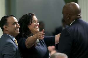 """Assemblywoman Lorena Gonzalez Fletcher, D-San Diego, flanked by Assemblyman Ash Kalra, D-San Jose, left, goes to hug Assemblyman Jim Cooper, D-Elk Grove, for his vote for the """"sanctuary state"""" bill she carried in the Assembly Friday, Sept. 15, 2017, in Sacramento, Calif. The Assembly approved the bill, SB54, by Senate President Pro Tem Kevin de Leon, D-Los Angeles, that would limit police cooperation with federal immigration authorities. It now goes to the Senate for final approval.(AP Photo/Rich Pedroncelli)"""