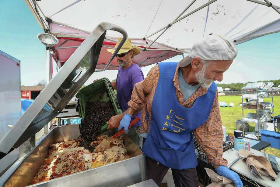 Randall Ediger, Santa Cruz, CA (left) and Richard Rawski, Madison Wisconsin prepare dinner with donated food on a mobile kitchen behind the Oak Meadows Community Worship Center 6105 Allendale Rd., Thursday, Sept. 14, 2017, in Houston. The members of the Family of Friends Relief Effort (F.F.R.E) and other volunteers are a group of rainbows children that formed after meeting at a Rainbow Gathering in 2004. They decided to use their know-how of cooking for huge groups of people to feed those affected by natural disasters. They've been at Hurricane Sandy and other places, and have already provided a couple thousand meals since landing, with plans to be here for a month. Photo: Steve Gonzales, Houston Chronicle / © 2017 Houston Chronicle