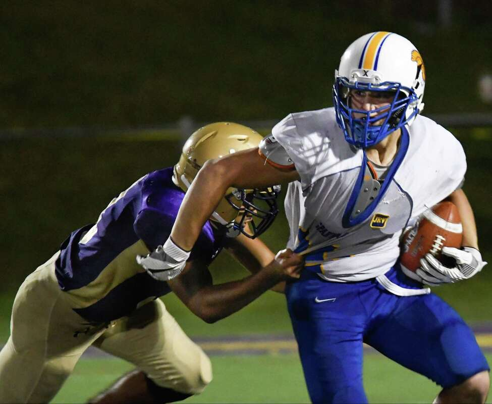 Amsterdam's Mikey Gomez tackles Queensbury's Nico Mattia during a game on Senior Night, Friday in Amsterdam, N.Y. (Jenn March/Special to the Times Union)