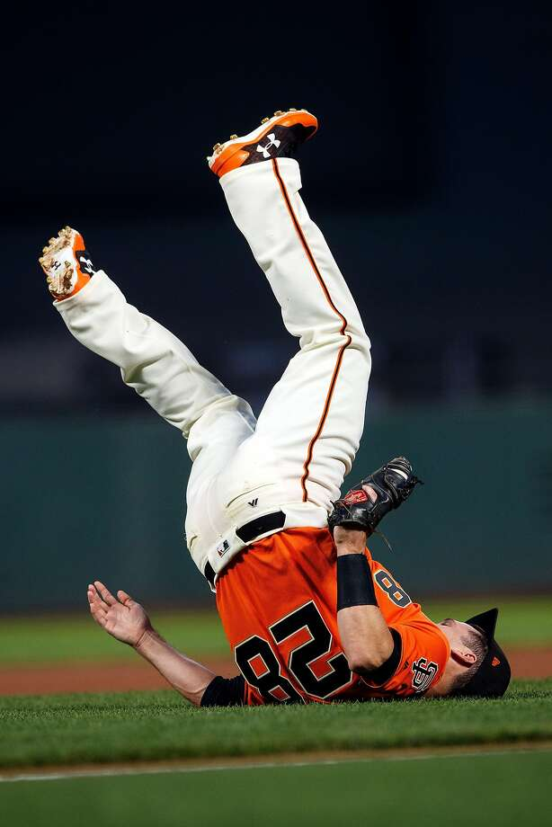 Buster Posey falls backwards after catching a fly ball hit off the bat of Jake Lamb. Photo: Jason O. Watson, Getty Images