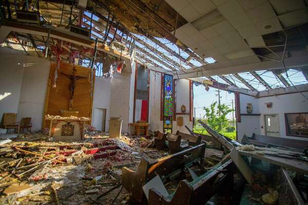 Father John Tran Nguyen stands inside the destroyed building of St. Peter's Catholic Church in Rockport, TX, Friday, Sept. 15, 2017. Hurricane Harvey destroyed the church when it came ashore August 25. The church has services in Vietnamese and English.