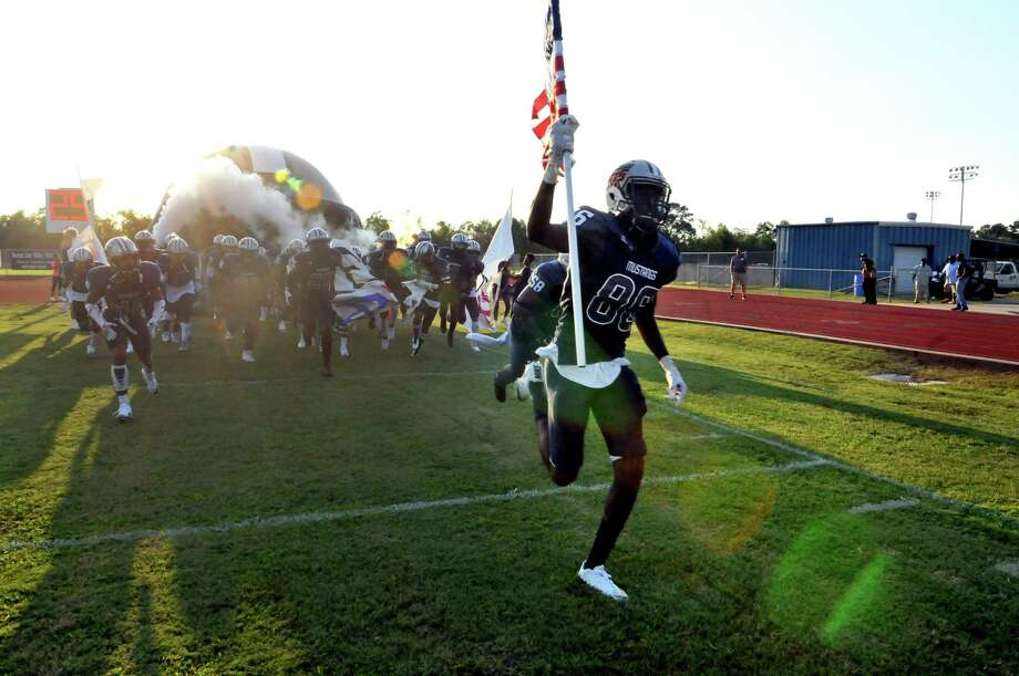 West Orange-Stark's Jaylon Mims carries the U.S. flag into Dan R. Hooks Stadium as the Mustangs make their entrance prior to Friday's game with Bridge City in West Orange. (Mike Tobias/The Enterprise)