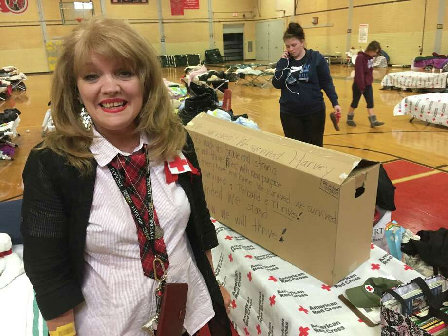 Rhonda Wood, a teacher at St. Mary's Catholic School in Orange, temporarily lost her home and has been teaching children at her shelter at Thomas Jefferson Middle School in Port Arthur, using a portable library. Photo: Tim Collins