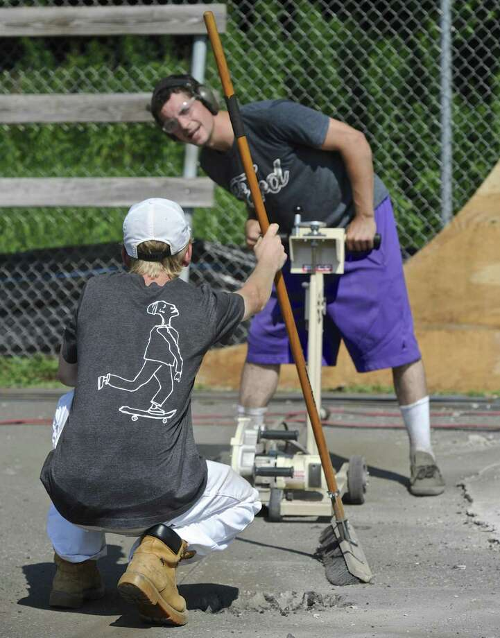 Russell Parker, of Sherman, gets help lining up a saw from Tristan Cornelis, of New Milford, while working to bring the New Milford Skate Park up to code. Thursday, August 3, 2017, in New Milford, Conn. Photo: H John Voorhees III / Hearst Connecticut Media / The News-Times