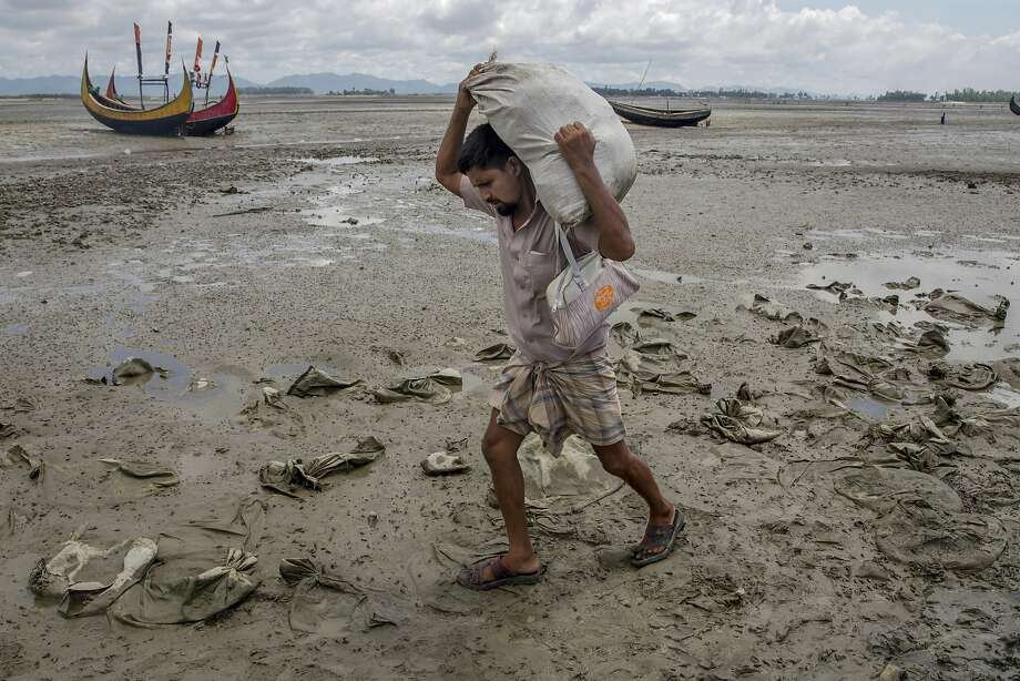 "A Rohingya Muslim, who crossed over from Myanmar into Bangladesh, walks towards the nearest refugee camps carrying his belongings at Teknaf, Bangladesh, Saturday, Sept. 16, 2017. United Nations agencies say an estimated 409,000 Rohingya Muslims have fled to Bangladesh since Aug. 25, when deadly attacks by a Rohingya insurgent group on police posts prompted Myanmar's military to launch ""clearance operations"" in Rakhine state. Those fleeing have described indiscriminate attacks by security forces and Buddhist mobs. (AP Photo/Dar Yasin) Photo: Dar Yasin, Associated Press"