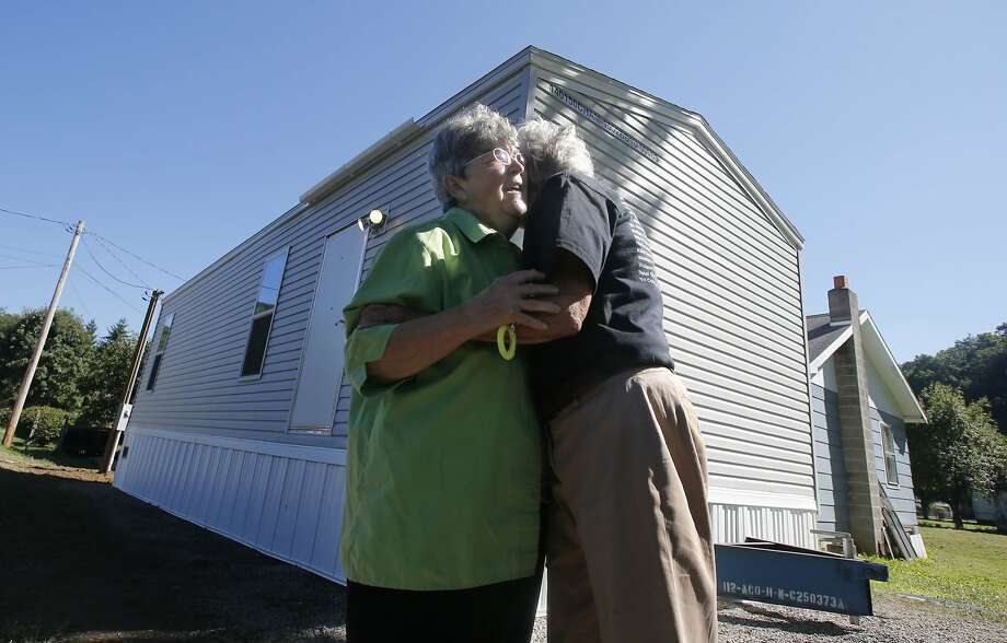 "FILE -  In this Aug. 23, 2016, file photo, Mayor Andrea ""Andy"" Pendleton, right, hugs resident Linda Bennett in front of Bennett's new FEMA trailer installed in front of her flood ravaged home in Rainelle, W. Va. Just before Hurricane Harvey made landfall in Texas in August 2017 as a Category 4 hurricane and in the floods that ensued, the federal government was auctioning off used disaster-response trailers at fire-sale prices. (AP Photo/Steve Helber, File) Photo: Steve Helber, Associated Press"