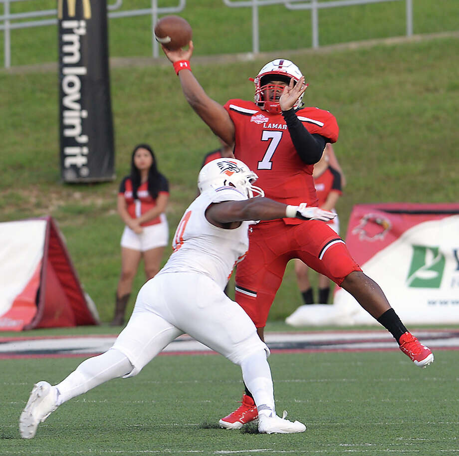 Lamar's Darrel Colbert, Jr., fires off a downfall pass as a UT Permian Basin defender tackles during Saturday's season home opener. The Cardinals game was free entry, with the stands largely full by the end of the first quarter. It was among the ways the university is trying to give back to the community, offering a taste of normal life for citizens and students alike in the wake of Tropical Storm Harvey. Photo taken Saturday, September 9, 2017 Kim Brent/The Enterprise Photo: Kim Brent / BEN