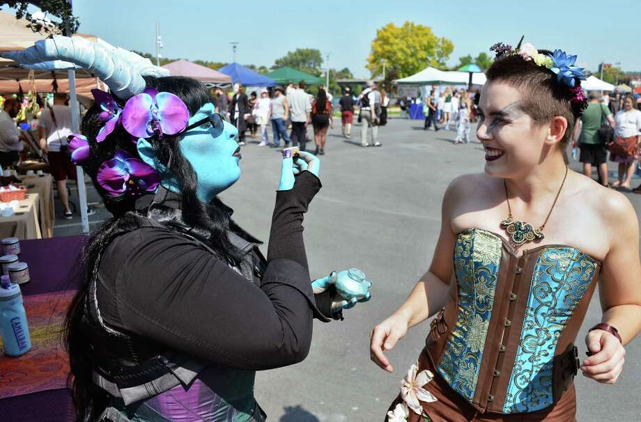 Fairy Apothecary Luaren Ouellette-Bruchez, left, blows some of her fury dust over Hannah Johnson of Troy during the Enchanted City Steampunk Festival Saturday Sept. 16, 2017 in Troy, NY.  (John Carl D'Annibale / Times Union) Photo: John Carl D'Annibale / 20041347A