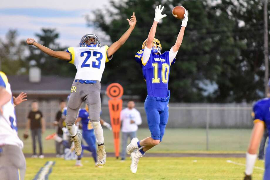 Hale Center's Jace Cannon, 10, leaps high to intercept a pass intended for Boys Ranch's Zack Barker, 23, during a football game in Hale Center Friday night. The Owls defeated Boys Ranch, 42-12, for their third consecutive victory to start the season. Photo: Photo Courtesy Of Albert Gomez Photography