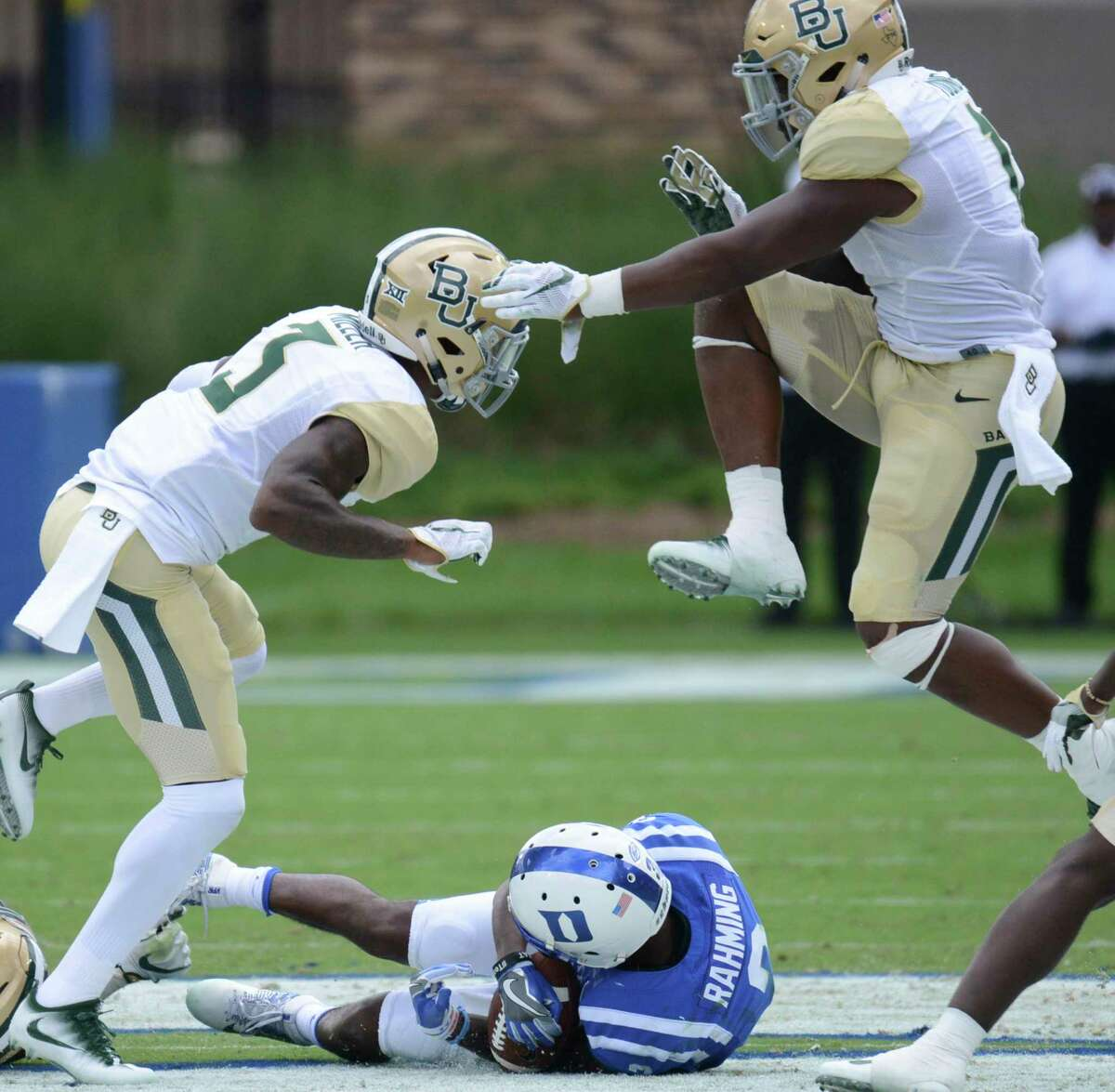 Baylor's Chad Kelly, left, and Davion Hall jumps over Duke's T.J. Rahming after a first down during an NCAA college football game, Saturday , Sept. 16, 2017, in Durham, N.C. (Bernard Thomas/The Herald-Sun via AP)