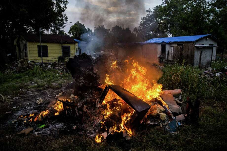 A woman burns the flooded contents of her living room behind her home on Jackson Quarters Lane that was flooded by two and a half feet of water after Hurricane Harvey Tuesday, Sept. 12, 2017 outside Wharton. ( Michael Ciaglo / Houston Chronicle) Photo: Michael Ciaglo, Staff / Houston Chronicle / Michael Ciaglo
