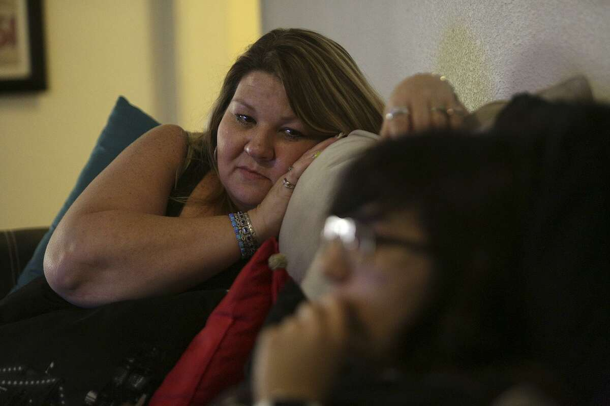 Kimberly Kowalik watches her daughter, Mercedez Montemayor, as she watches televison on Tuesday, August 29, 2017, the one-year anniversary of the carjacking.