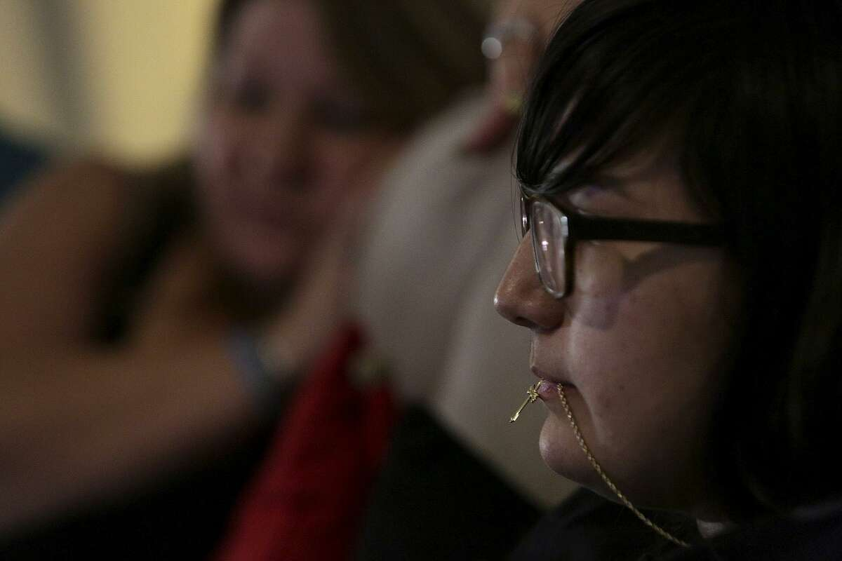 Mercedez Montemayor holds a cross on a necklace between her lips as she watches televison with her mother, Kimberly Kowalik, on Tuesday, August 29, 2017, the one-year anniversary of the carjacking.