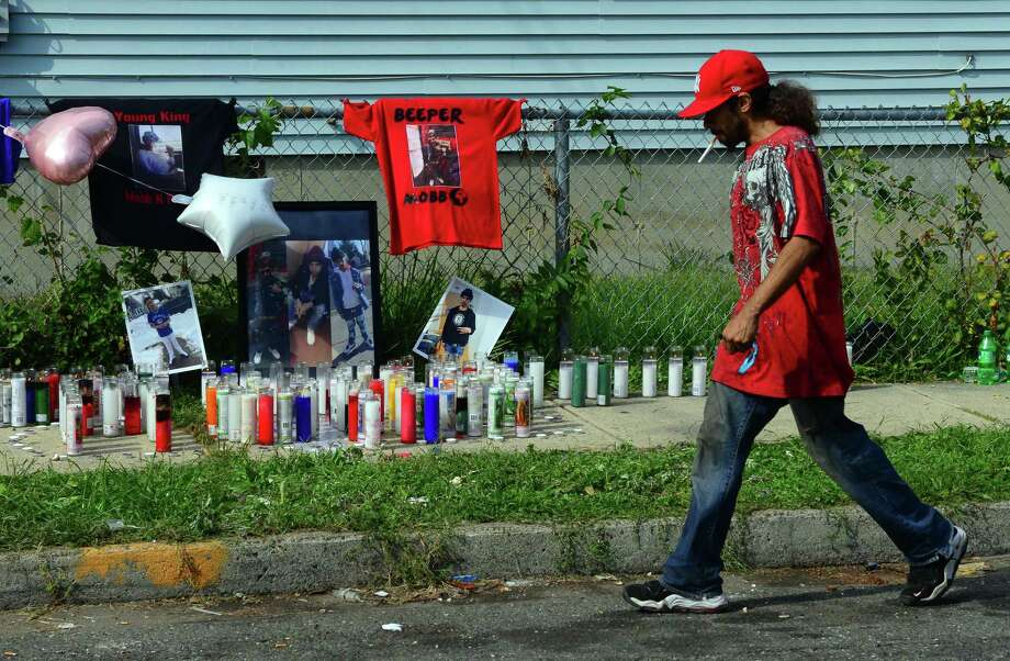 A pedestrian passes a memorial for shooting victim Eric Diaz that was erected on Beardsley Street in Bridgeport, Conn. on Thursday Sept. 15, 2017. Bridgeport police spokesman Av Harris said the 19-year-old Diaz was shot dead Thursday around 11 p.m. Diaz was found shot in the stomach after police responded to a report of shots fired at the intersection of Beardsley Street and Newfield Avenue. Photo: Christian Abraham / Hearst Connecticut Media / Connecticut Post