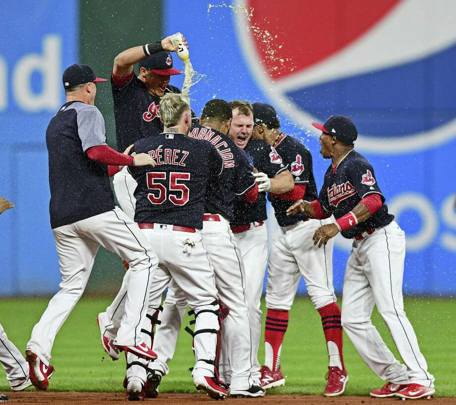 Cleveland Indians' Jay Bruce, center, celebrates with teammates after Bruce drove in the winning run with a double off Kansas City Royals relief pitcher Brandon Maurer during the 10th inning of a baseball game, Thursday, Sept. 14, 2017, in Cleveland. The Indians won 3-2. (AP Photo/David Dermer) / AP 2017