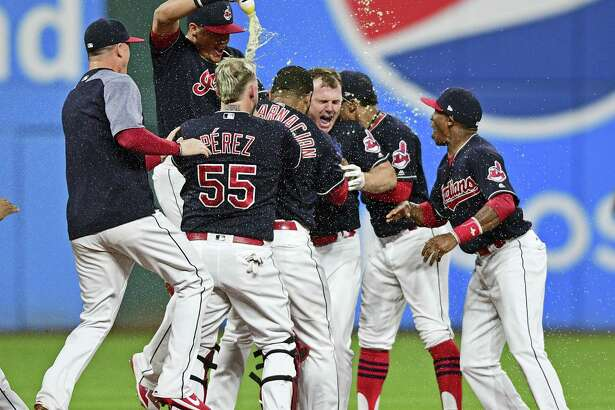 Cleveland Indians' Jay Bruce, center, celebrates with teammates after Bruce drove in the winning run with a double off Kansas City Royals relief pitcher Brandon Maurer during the 10th inning of a baseball game, Thursday, Sept. 14, 2017, in Cleveland. The Indians won 3-2. (AP Photo/David Dermer)