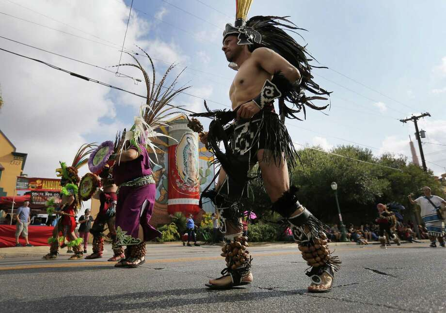 Members of Grupo Azteca Teocalli perform a ceremonial dance to start off the parade to commemorate Mexico's Independence Day on Saturday, Sept. 16, 2017. Avenida Guadalupe Association hosted its 36th annual parade and festival to commemorate Dieciseis in the heart of the Westside on Saturday. Parade watchers saw a variety of floats, political officials, high school bands, children's organizations, senior groups and dancers which filed slowly along Guadalupe Street near the Guadalupe Theater and finished a few blocks further down the road. Some parade attendees carried Mexican flags to honor the day, 207 years ago, that Mexico established its independence from Spain. Celebrations continued throughout the day at the Plaza Guadalupe. (Kin Man Hui/San Antonio Express-News) Photo: Kin Man Hui, Staff / San Antonio Express-News / ©2017 San Antonio Express-News