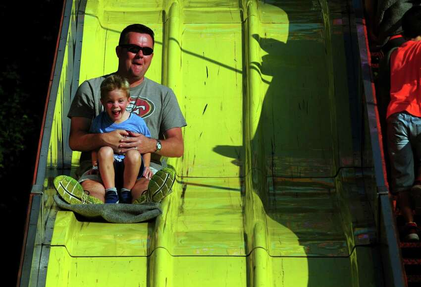 Tom Boland, of Fairfield, rides down the Super Slide with his son Mikey, 5, during Our Lady of Assumption Church's 24th Annual SeptemberFest fair on the church grounds in Fairfield, Conn., on Saturday June 17, 2017. The annual family fair continues on Sunday, 1 PM to 6 PM. For more information about the fair go to: http://www.olaffld.org/SeptemberFest