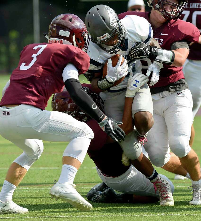 Capital Prep Tremayne Garrett II is stopped by a host of St. Luke's defenders including Austin Anderson (3)during a FAA varsity football game at Watson Field at Pedrick Stadium on Saturday, Sept. 16, 2017 in New Canaan, Connecticut. Capital Prep Harbor defeated St. Luke's 46-0.