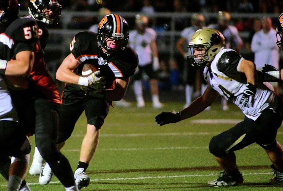 Shelton's Jack Carr runs through the Daniel Hand defense on Friday night. Photo: Christian Abraham / Hearst Connecticut Media / Connecticut Post