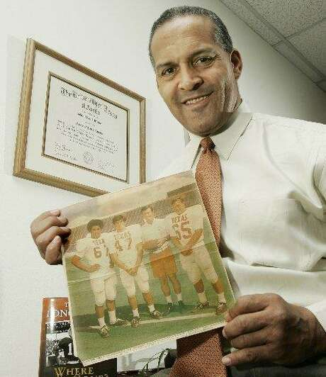 Dallas attorney and former Texas Longhorn Julius Whittier holds a newspaper clipping from 1971 featuring Whittier with teammates Bruce Cannon, Greg Dahlberg, and coach Darrell Royal, Friday afternoon, Dec. 16, 2005 in Dallas. Photo: Tim Sharp /AP Photo