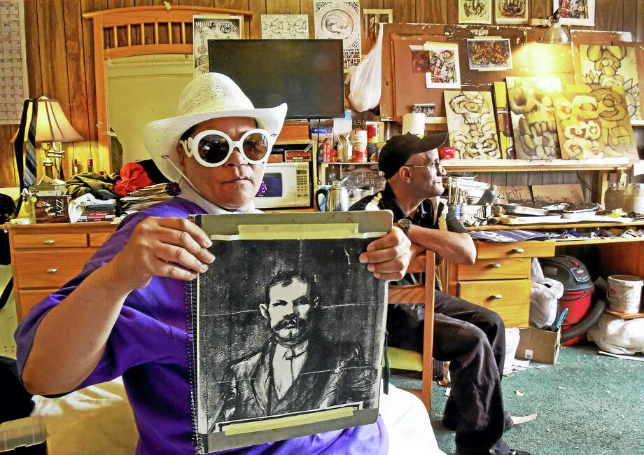 Elaine Sands, 66, left, holds a portrait of the great-grandfather of  artist/illustrator Kevin Sanchez Walsh, with Stacey Lewis, 52, in a room of at the Duncan Hotel on Chapel Street in New Haven that is the home and studio of Mr. Walsh. Sands and Lewis, along with Walsh,  are long-term residents of the affordable Duncan Hotel who must leave because it is will be developed as an upscale boutique hotel. Photo: Peter Hvizdak /  Hearst Media Connecticut / New Haven Register