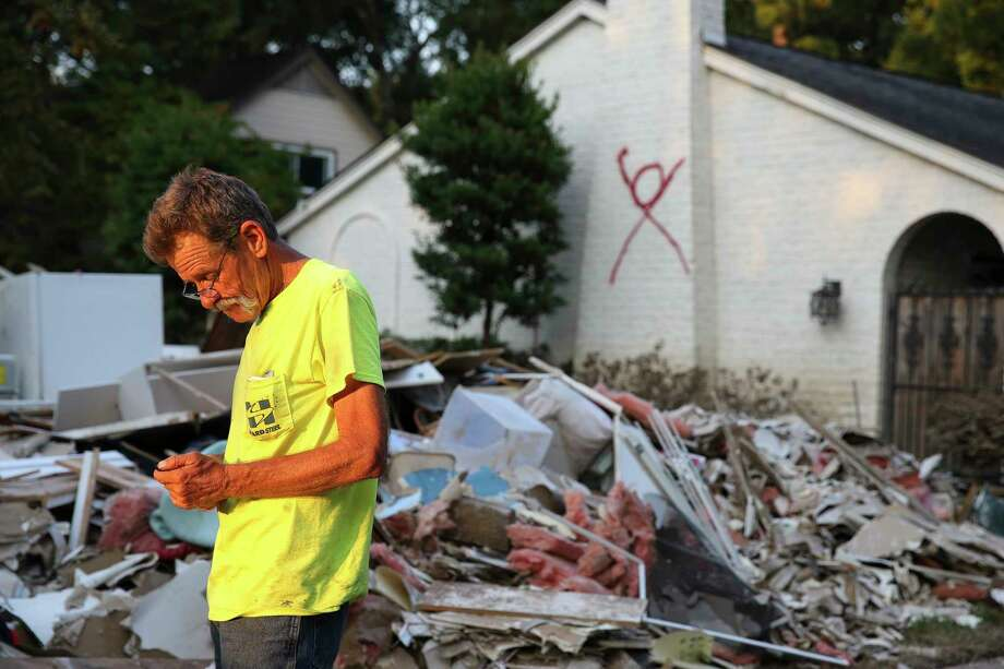 Contractor Ricky Green of Alabama finishes a day of picking up large debris in  a Memorial-area neighborhood after Hurricane Harvey devastated the area in 2017. A red X signifying that someone died inside still marks Robert Arthur Haines' house on Langwood. Photo: Yi-Chin Lee, Staff / © 2017  Houston Chronicle