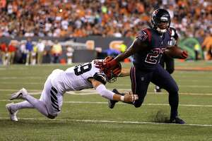 Texans running back D'Onta Foreman, right, shakes a tackle by Bengals outside linebacker Nick Vigil while picking up a few of his 40 rushing yards during Thursday's victory in Cincinnati.