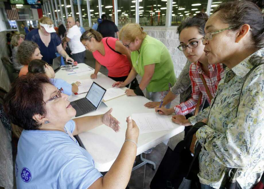 Volunteer Maria Santiago, left, with Baker Hughes Hispanic forum, talks with Gigi Gomez, center, and her mother, Ana Gomez, right, Saturday during the bilingual recovery fair. Photo: Melissa Phillip, Houston Chronicle / © 2017 Houston Chronicle