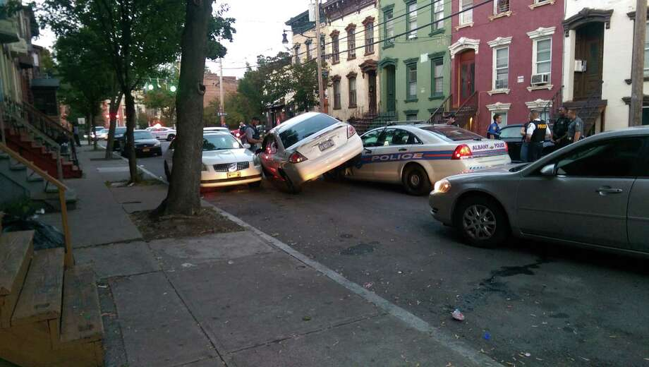 Police say a woman drove her car on top of the police vehicle on Lark Street Saturday evening. Photo: Jason Kraus