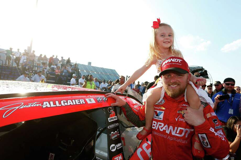 JOLIET, IL - SEPTEMBER 16:  Justin Allgaier, driver of the #7 BRANDT/Celebrating the Future of AG Chevrolet, and his daughter Harper Grace pose with the winner?s decal on his car in Victory Lane after winning the NASCAR XFINITY Series TheHouse.com 300 at Chicagoland Speedway on September 16, 2017 in Joliet, Illinois.  (Photo by Brian Lawdermilk/Getty Images) Photo: Brian Lawdermilk, Stringer / 2017 Getty Images