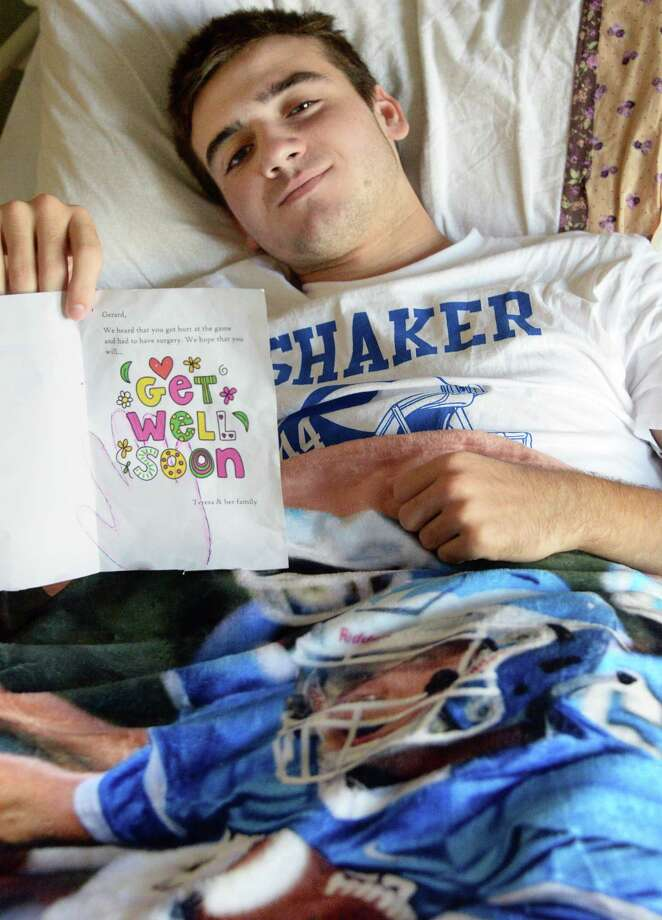 Covered by a blanket with a picture of him playing, Shaker running back Gerard Rhatigan holds a a get well card from the little girl he saved from drowning as he recovers in his hospital room at Sunnyview Rehabilitation Friday Sept. 15, 2017 in Schenectady, NY.  (John Carl D'Annibale / Times Union) Photo: John Carl D'Annibale / 40041563A
