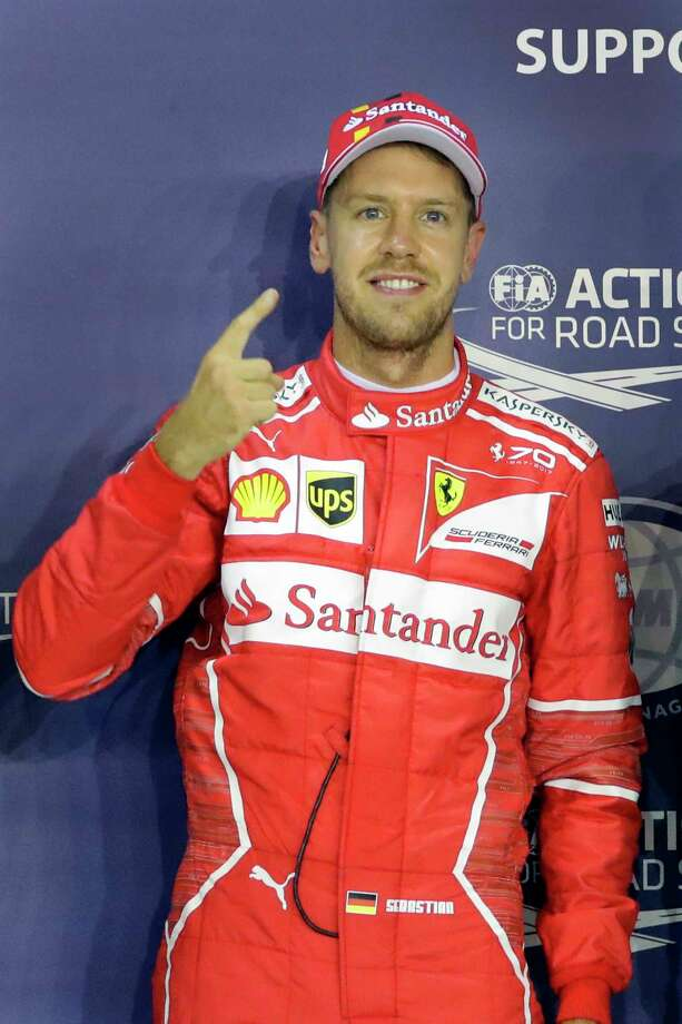 Ferrari driver Sebastian Vettel of Germany, center, celebrates after taking pole position during the qualifying session for the Singapore Formula One Grand Prix on the Marina Bay City Circuit Singapore, Saturday, Sept. 16, 2017. (AP Photo/Wong Maye-E) ORG XMIT: XWM114 Photo: Wong Maye-E / Copyright 2017 The Associated Press. All rights reserved.