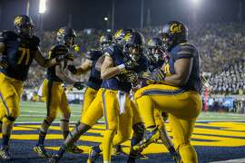 California Golden Bears running back Patrick Laird (center) celebrates his touchdown run during the first quarter of an NCAA football game between the California Golden Bears and the Mississippi Rebels at California Memorial Stadium on Saturday, Sept. 16, 2017, in Berkeley, in Berkeley, Calif. The Rebels lead 16-7 at halftime.