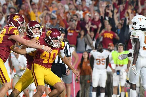 USC kicker Chase McGrath (40) is mobbed by teammates after kicking the game-winning field goal in overtime against Texas at the Los Angeles Memorial Coliseum on Saturday, Sept. 16, 2017. (Wally Skalij/Los Angeles Times/TNS)