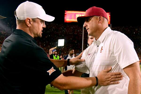 LOS ANGELES, CA - SEPTEMBER 16:  Head coach Clay Helton of the USC Trojans meets head coach Tom Herman of the Texas Longhorns at the end of the game after a 27-24 Trojan win in overtime at Los Angeles Memorial Coliseum on September 16, 2017 in Los Angeles, California.  (Photo by Harry How/Getty Images)