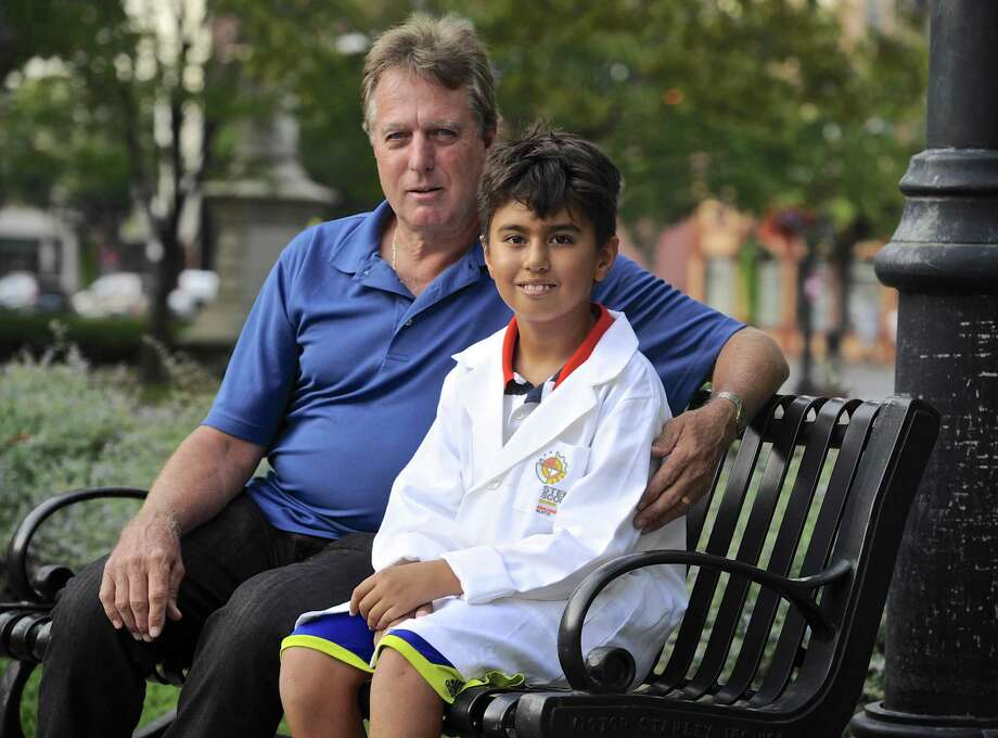 Gary Prybylski Jr, 9, of Danbury, and his father Gary Prybylski Sr sit on a bench in front of the Danbury Public Library on Tuesday afternoon, September 20, 2016, in Danbury, Conn. The library is meeting place of the new STEM Scouts Danbury Library Elementary School Lab #1010, which is part of the Boy Scouts. Prybylski Sr brought the new scouting program to Danbury. Photo: H John Voorhees III / Hearst Connecticut Media / The News-Times
