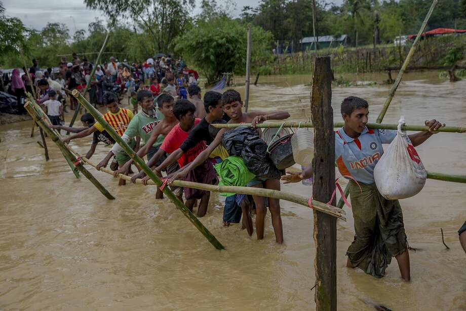 Rohingya Muslims, who crossed over from Myanmar into Bangladesh, use a makeshift footbridge near Balukhali refugee camp, Bangladesh, Sunday, Sept. 17, 2017. Bangladeshi authorities on Sunday took steps to restrict the movement of Muslim Rohingya refugees living in crowded border camps after fleeing violence in Myanmar, while that nation's military chief maintained the chaos was the work of extremists seeking a stronghold in the country. (AP Photo/Dar Yasin) Photo: Dar Yasin, Associated Press
