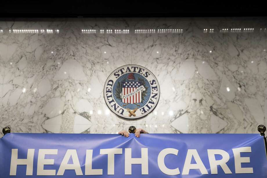 "A staffer adjusts a banner reading ""healthcare is a right"" before Sen. Bernie Sanders (I-Vt.) holds a news conference regarding health care policy, on Capitol Hill in Washington, Sept. 13, 2017. On the same day that Republican lawmakers were pitching a last-gasp effort to undo the Affordable Care Act, Sanders said that 15 Democratic senators have signed on to what he called a ""a Medicare-for-all, single-payer health care system."" (Tom Brenner/The New York Times) Photo: TOM BRENNER / NYT / NYTNS"