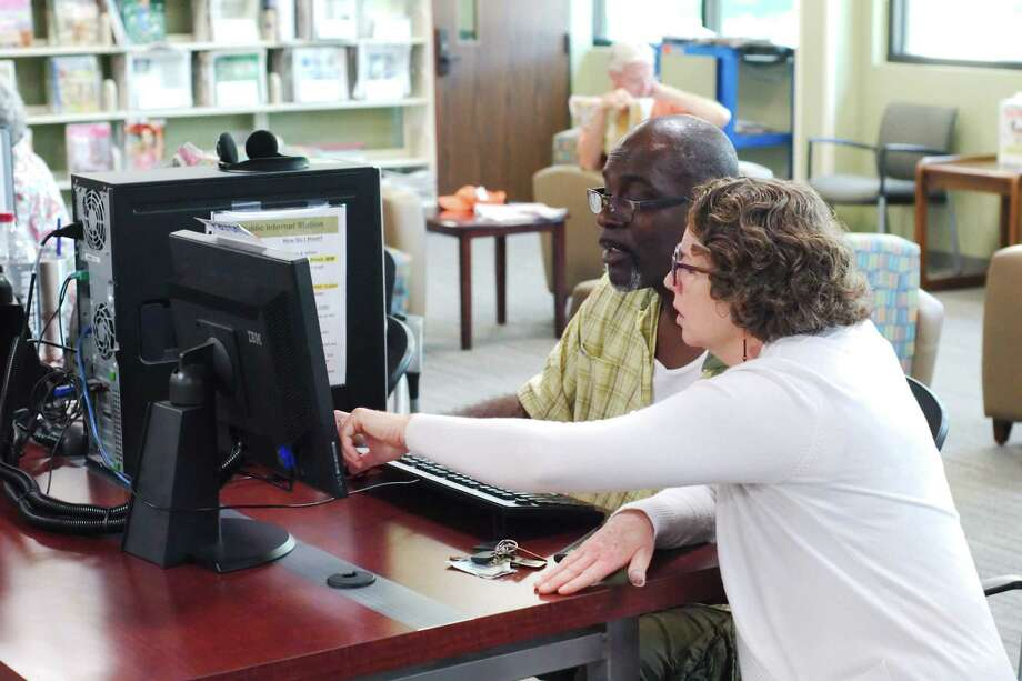 Reference Librarian Kim Zrubek assists John Martin with disaster loan assistance in the computer work area at the Friendswood Public Library. Photo: Kirk Sides / © 2017 Kirk Sides / Houston Chronicle
