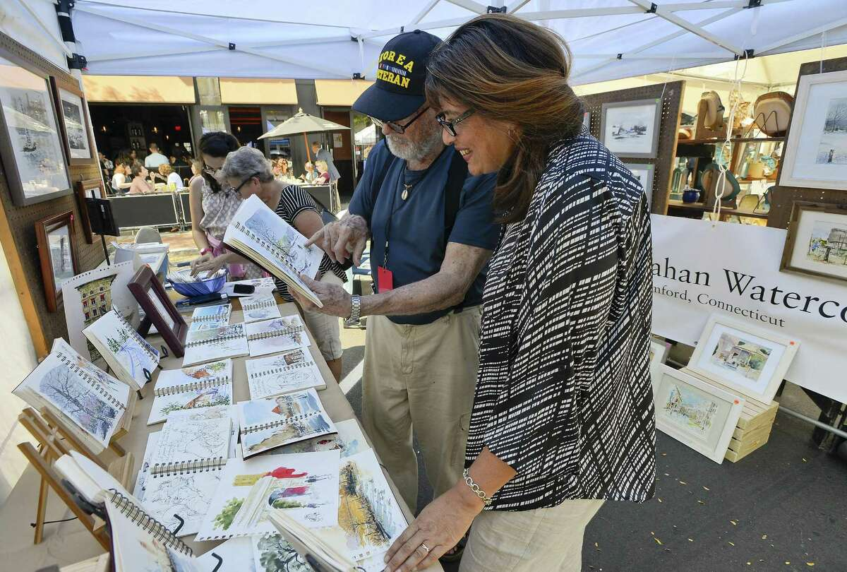 Stamford artist Bob Callahan talks about his works with Margarita Ucero of Stamford during the Arts & Crafts on Bedford event on Saturday, Sept. 16, 2017 in Stamford, Connecticut. Visitors explored various craft and artisan boutiques by artists, local and a far, on Bedford Street.