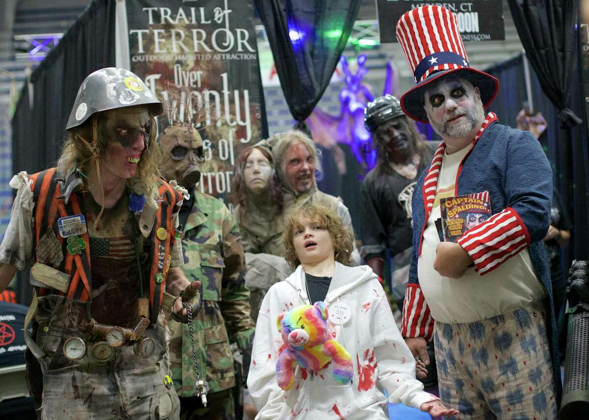Peyton Vesneski, 12, poses with a group of ghoulish creatures at the Connecticut HorrorFest on Saturday at the Danbury Arena.