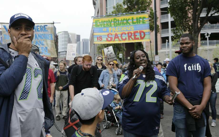 Katrina Johnson, second from right, speaks outside CenturyLink Field after a taking part in a march supporting Black Lives Matter and other social causes before an NFL football game between the Seattle Seahawks and the San Francisco 49ers, Sunday, Sept. 17, 2017, in Seattle. Johnson is wearing the #72 jersey of Seahawks defensive end Michael Bennett, who has been a vocal supporter of various social issues, and who reached out to her family after Johnson's cousin, Charleena Lyles, was fatally shot by Seattle Police earlier in the year. (AP Photo/John Froschauer) Photo: John Froschauer/AP