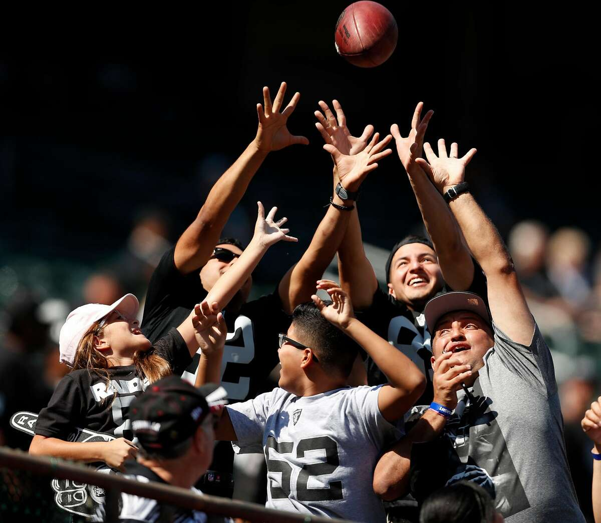 Oakland Raiders' fans try to catch a ball thrown by Cordarrelle Patterson before Raiders play the New York Jets during NFL game at Oakland Coliseum in Oakland, Calif., on Sunday, September 17, 2017.