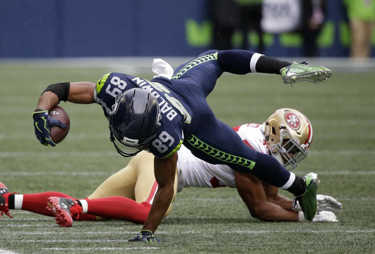 Seattle Seahawks wide receiver Doug Baldwin reaches for yardage after he was tackled by San Francisco 49ers strong safety Eric Reid, right, in the first half of an NFL football game, Sunday, Sept. 17, 2017, in Seattle. (AP Photo/Elaine Thompson)