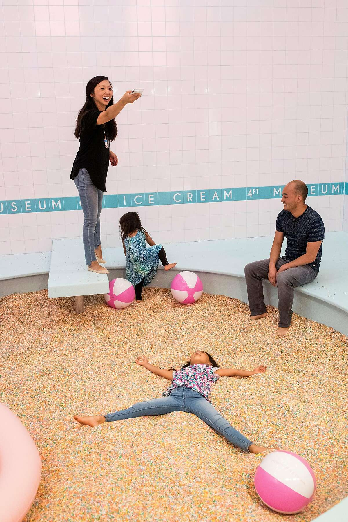 Amy Kim (left) snaps photos of her daughter Adele Kim playing in a pool of sprinkles at the Museum of Ice Cream in San Francisco, Calif., on Sunday, September 17, 2017. The pop-up exhibit opened to the public on Sunday.