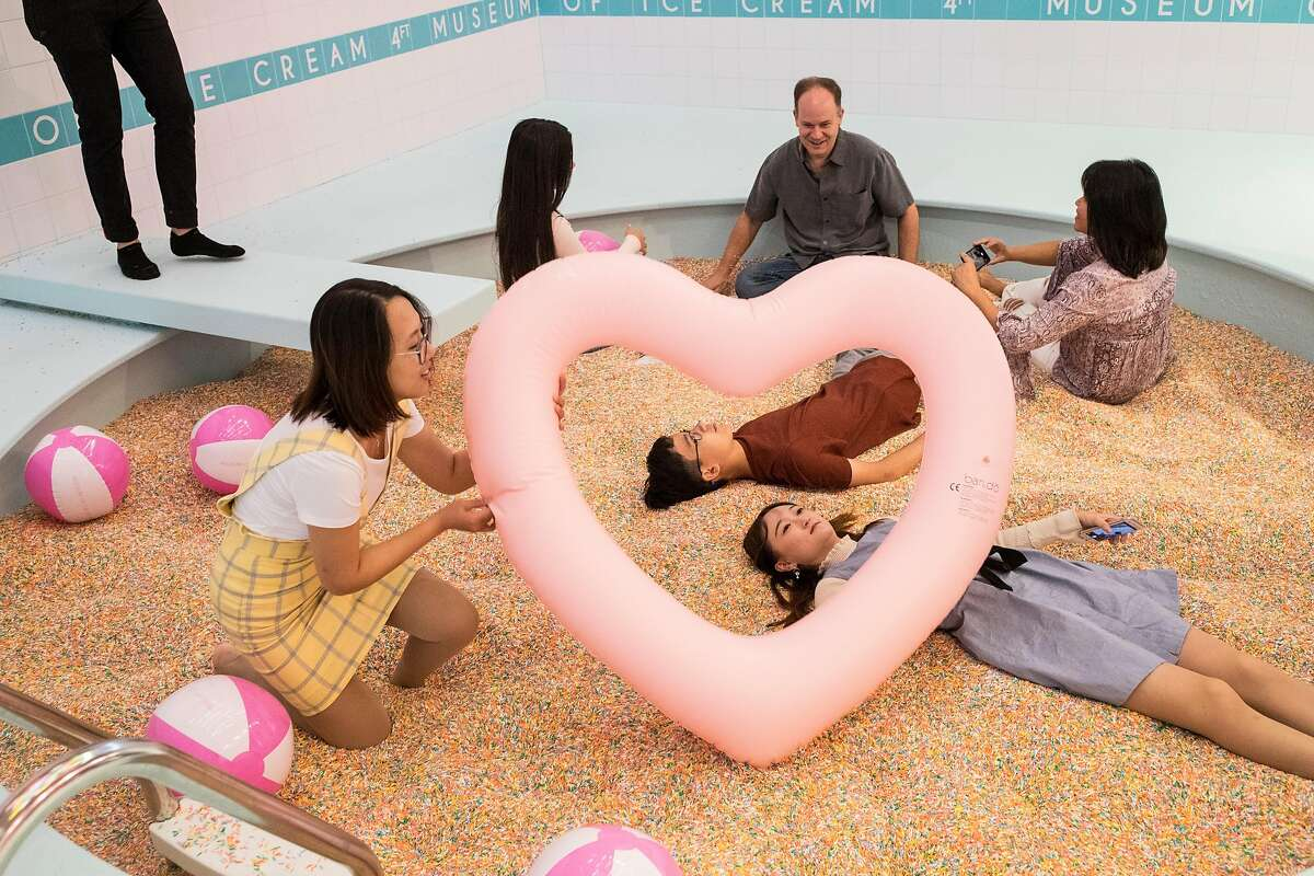 Visitors to the Museum of Ice Cream play in a pool of sprinkles at the pop-up exhibit in San Francisco, Calif., on Sunday, September 17, 2017. The Sprinkle Pool is filled with sprinkles made with antimicrobial plastic.