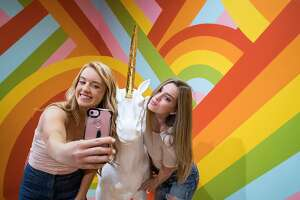 Taylor Sowers (left) snaps a selfie with a unicorn and Mary Hinek while visiting the Museum of Ice Cream in San Francisco, Calif., on Sunday, September 17, 2017. The pop-up exhibit opened to the public on Sunday.